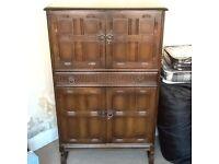 Solid dark oak drinks cabinet .