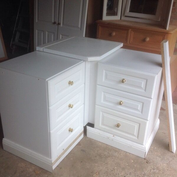 Magnet fitted bedroom corner laundry unit with a three drawer unit each side