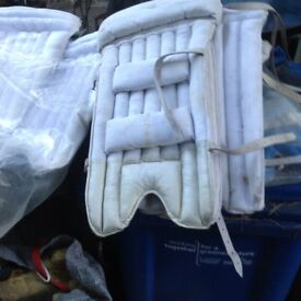 selection of cricket pads and gloves