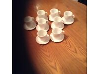 8 white China coffee cups and saucers.