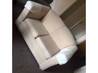 Two seater cream / beige fabric sofa