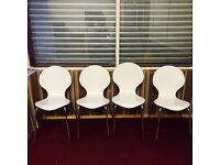 Four white wooden cafe or bistro chairs