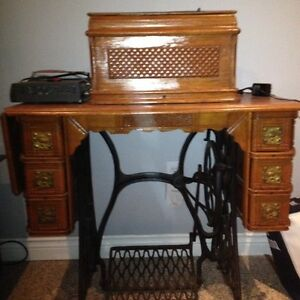 Antique sewing machine with wooden cover.  Singer