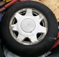 Complete set of 4 tires with rims and rubber for a Cadillac.