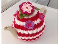 Red and white striped knitted tea cosy with summer flowers.