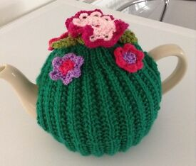 Green knitted tea cosy with summer flowers