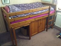 Bed with retractable table and cupboard
