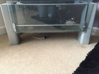 Grey/silver tv unit with glass shelf and front cover