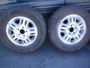 Set of two aluminum rims with tires.