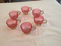 Set of 6 small rose coloured glass cups with gold metal handles