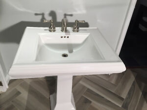 Kohler pedestal sink with fixtures.