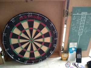 Red knight dart board with 6 darts in cabinet withchalk board