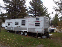 32 ft Travel Trailer on lot at campground close to Ottawa
