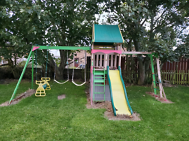 Wooden kids playhouse with slide, swings and monkey bar