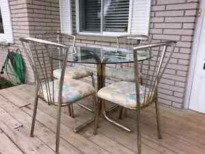 Vintage chrome table and four chairs glass top.