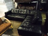 Black leather corner sofa and large foot stool