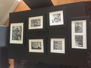 7 various sized black and white prints in black fames