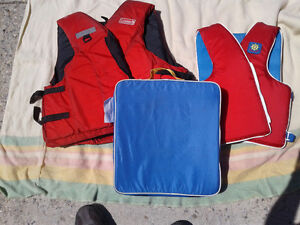 2 adult life jackets and one life saver seat cushion