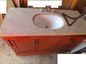 Wood Cabinet With A Granite Countertop And Sink With Faucet