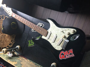 Squire Fender Stratocaster with amp and cords.