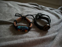 Two peace sign bracelets and a peace sign necklace.