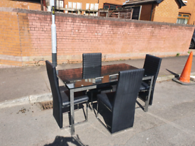 50. Black glass top table and 4 leather chairs