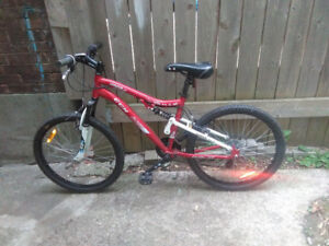 """CCM mountain bike with dual suspension and 24"""" tires."""