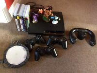 Sony PS3 console, 3 x controllers, 1x racing controller, 7x games , sky landers portal+characters