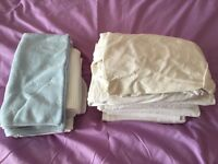 Bundle of Cot sheets and baby blankets.