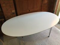 White oval table with 4 black chairs