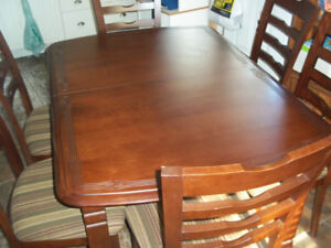 Walnut dinning room table, 6chairs and 1 leaf with top design.