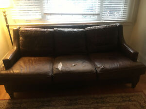 Brown leather sofa. Two cushions are ripped.