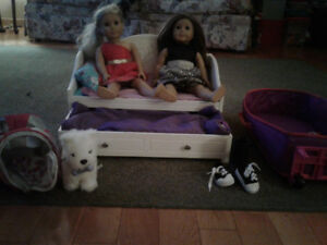 2 American girl dolls a pet dog a trundle bed and a carrying cas
