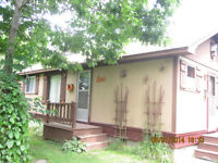 COTTAGE AND CAMPER ALL IN ONE TWO MINUTES SANDY  BEACH AND LOT