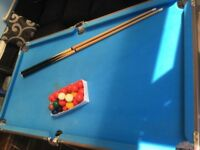 Pool table with balls and 2 cues