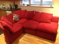 Large red corner sofa with footstool