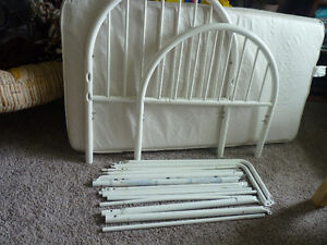 White metal toddler bed and sheets