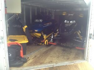 Two Snowmobiles And An Enclosed Trailer