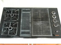 Gas stove top with two burners and a grill
