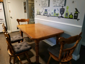 Solid wood dining room table with 4 matching chairs and 2 leafs.