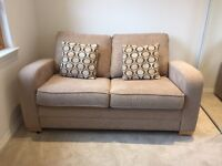 Cream sofa bed with Spring action mechanism.