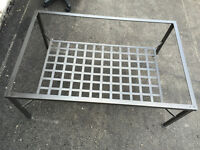 Metal coffee table with thick glass tabletop.