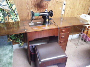 Singer sewing machine in solid wood cabinet antique