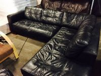 Black leather corner sofa with large footstool