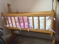 Swinging wooden crib with cot sides, mattress and sheets
