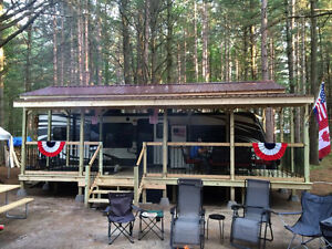 Trailer with covered deck porch on a great campsite!