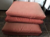 4 orange patio cushions for sale $30 for all.  Sun faded