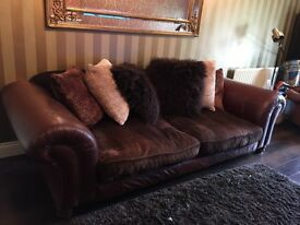 Large brown leather settee with fabric seats and cushions