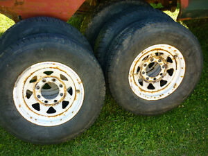 Four RoughRider LT 215 85R16's on Ford 8 bolt rims for sale.