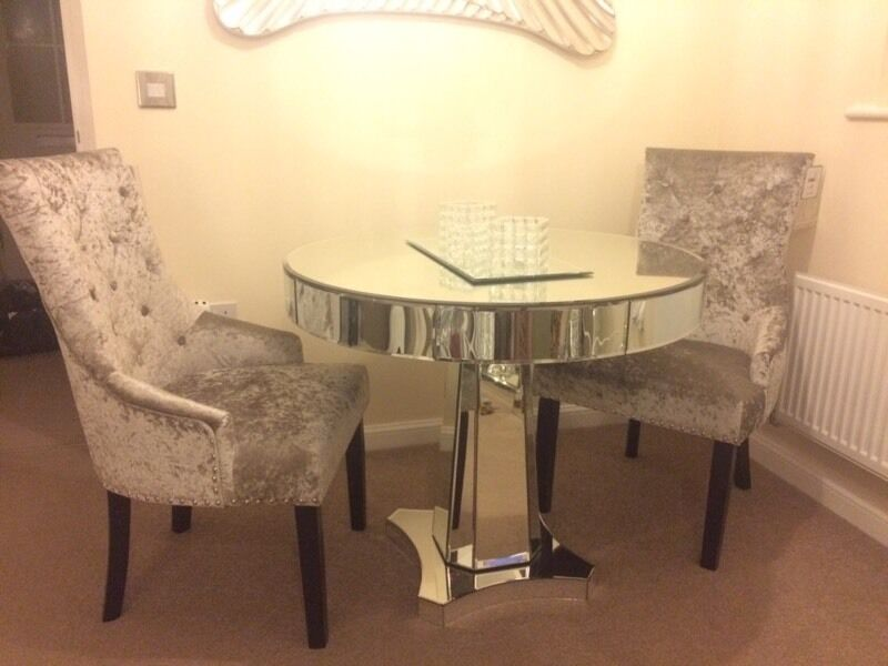 Mirrored glass dining table and two mink crushed velvet chairs